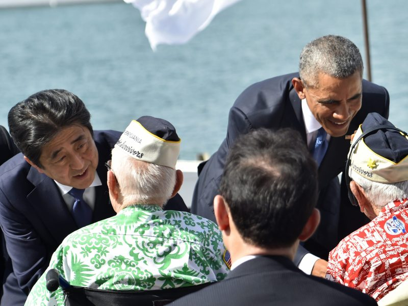 US President Barack Obama (R) and Japanese Prime Minister Shinzo Abe greet veterans at Kilo Pier overlooking the USS Arizona Memorial on December 27, 2016 at Pearl Harbor in Honolulu, Hawaii. Photo: AFP/Nicholas Kamm