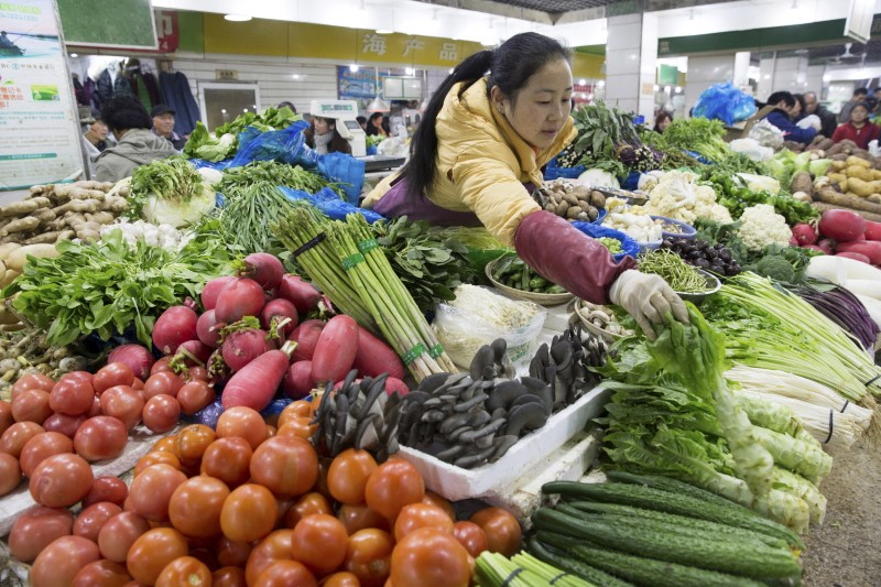 A vendor arranges vegetables at her stall at a market in Nanjing, Jiangsu province. Photo: Reuters/China Daily