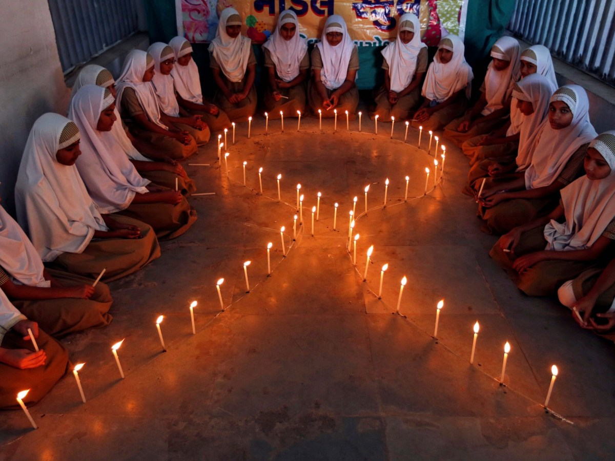 School girls light candles in the shape of a ribbon during a HIV/AIDS awareness campaign ahead of World Aids Day, in Ahmedabad, India November 30, 2016. Photo: Reuters/Amit Dave