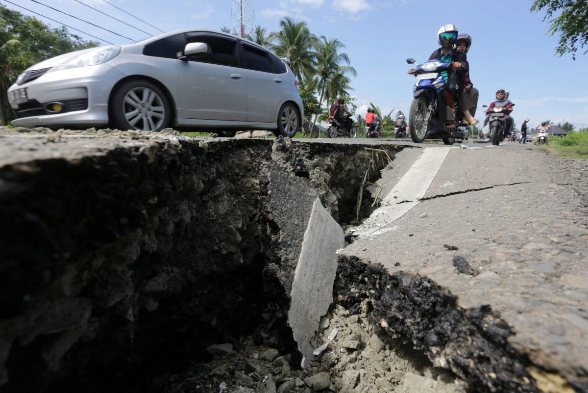 Motorcyclists pass a damaged section of a road in Meuredu, Pidie Jaya, in the northern province of Aceh, Indonesia. Photo: Antara Foto/ Irwansyah Putra/ via REUTERS