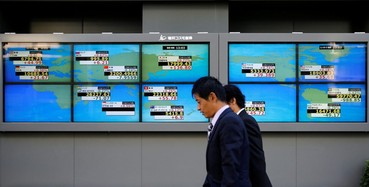 Men walk past an electronic board showing Japan's Nikkei average outside a brokerage in Tokyo, Japan, November 18, 2016. Photo: Reuters, Toru Hanai