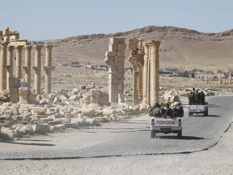 Syrian army soldiers drive past the Arch of Triumph in the historic city of Palmyra, in Homs Governorate, Syria in this April 1, 2016 file photo.  Reuters/Omar Sanadiki