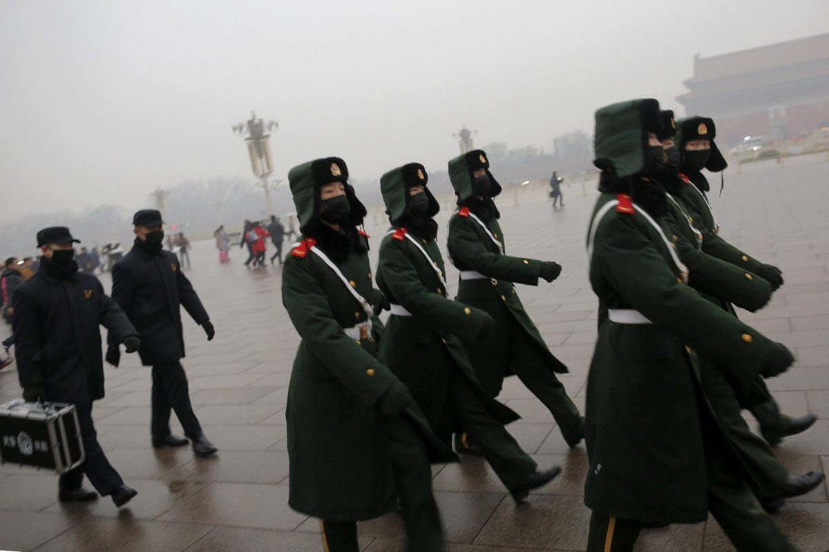 "Paramilitary policemen wearing masks march on a cold morning following a flag-raising ceremony amid heavy smog at Tiananmen Square, after the city issued its first ever ""red alert"" for air pollution, in Beijing December 9, 2015.  REUTERS/Damir Sagolj/File Photo"