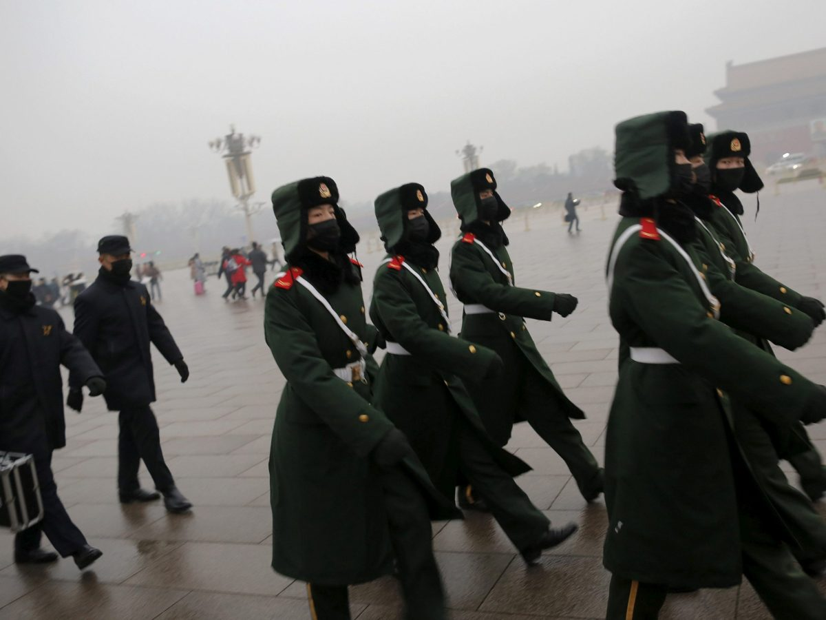 """Paramilitary policemen wearing masks march on a cold morning following a flag-raising ceremony amid heavy smog at Tiananmen Square, after the city issued its first ever """"red alert"""" for air pollution, in Beijing December 9, 2015.  REUTERS/Damir Sagolj/File Photo"""