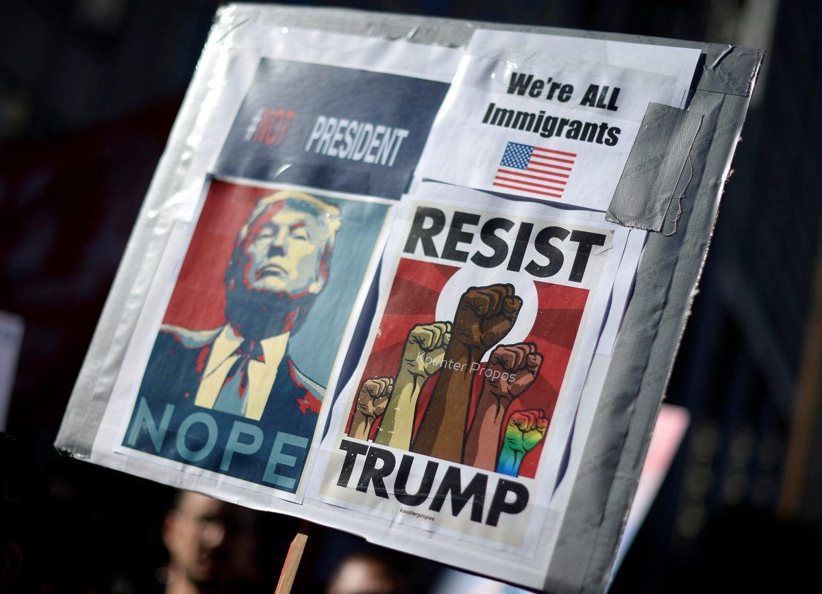 Protesters hold up signs during a march and rally against the United States President-elect Donald Trump in Los Angeles, California, U.S. December 18, 2016. REUTERS/Kevork Djansezian