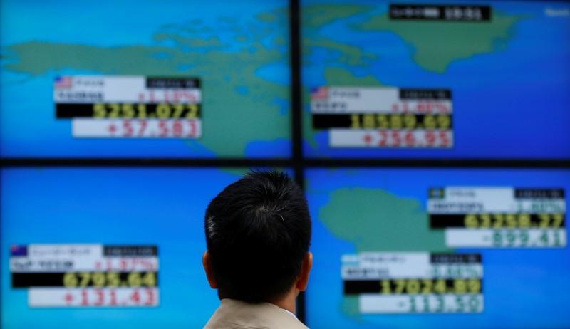 A man looks at a electronic board showing the Dow Jones average (top R) and NASDAQ average (top L) outside a brokerage in Tokyo, Japan, November 10, 2016.   REUTERS/Toru Hanai