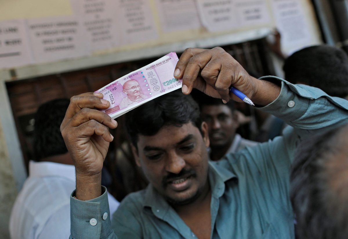 A man holds 2000 Indian rupees notes aloft outside a bank in Mumbai. Photo: Reuters
