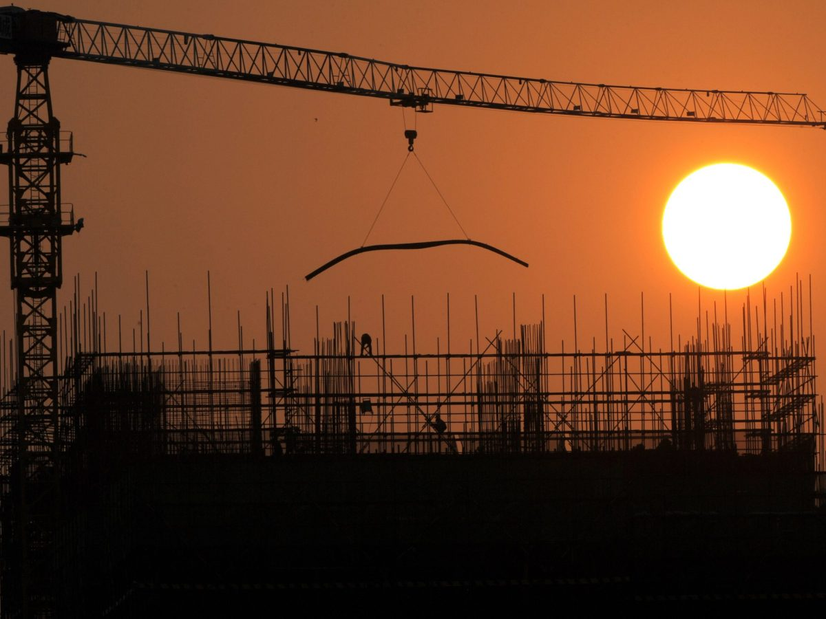 The sun rises over a building under construction in Phnom Penh. Photo: AFP / TANG CHHIN SOTHY