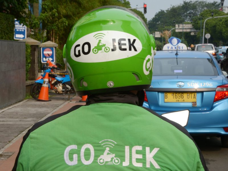A motorcycle driver with Indonesian start-up Go-Jek waiting for customers along a street in Jakarta. Photo: AFP, Adek Berry