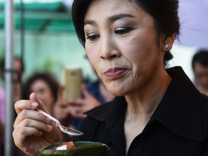 Former Thai prime minister Yingluck Shinawatra tries a rice dish during an event to promote the consumption of Thai rice to help struggling farmers, in her private garden in Bangkok on November 17, 2016.  The ex-premier is currently standing trial for negligence over a rice pledging scheme at the Constitutional Court. / AFP PHOTO / Lillian SUWANRUMPHA