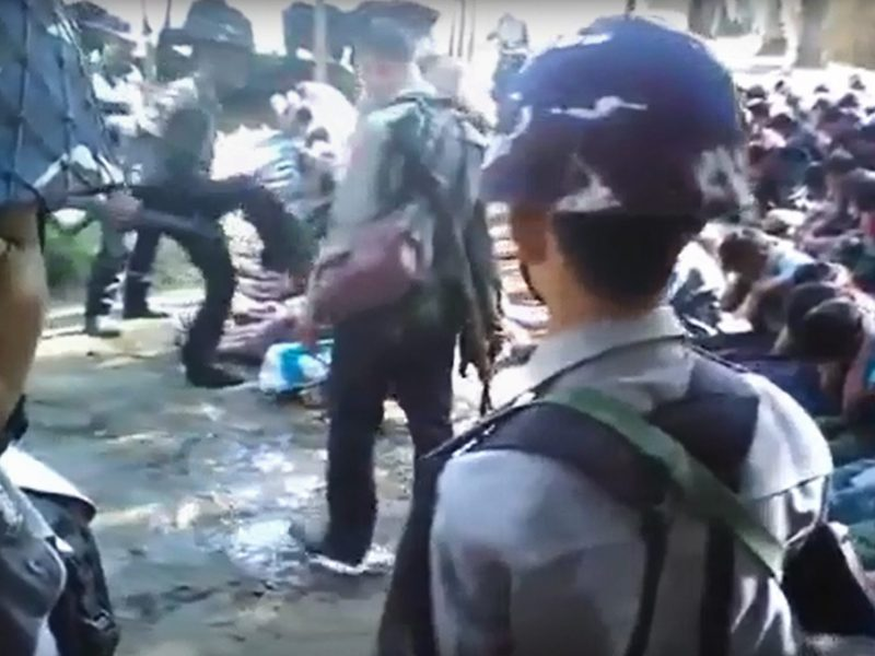 This screen grab taken on January 4, 2017 from a YouTube video originally taken by Myanmar Constable Zaw Myo Htike (pictured at far L - looking at camera) shows a policeman (back L) kicking out at a Rohingya minority villager seated on the ground with others, in the village of Kotankauk during a police area clearance operation on November 5, 2016. A commission probing violence in Myanmar's Rakhine State on January 4 denied security forces had abused Rohingya, days after a video emerged showing police beating civilians from the Muslim minority. Photo: AFP/YouTube/ Zaw Myo Htike