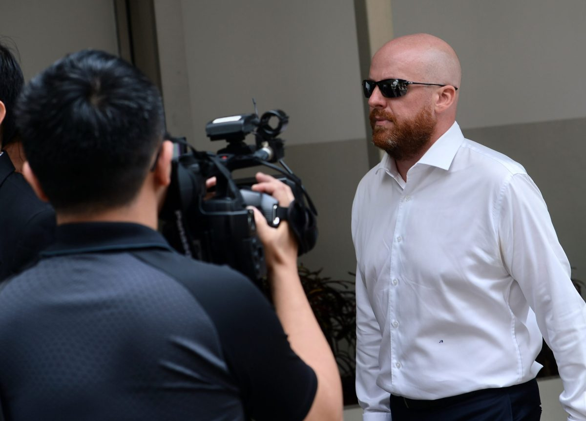 Swiss banker Jens Fred Sturzenegger (R) arrives at the state court in Singapore on January 11, 2017. Sturzenegger was expected to plead guilty to money laundering charges linked to Malaysia's 1MDB corruption scandal. / AFP PHOTO / ROSLAN RAHMAN
