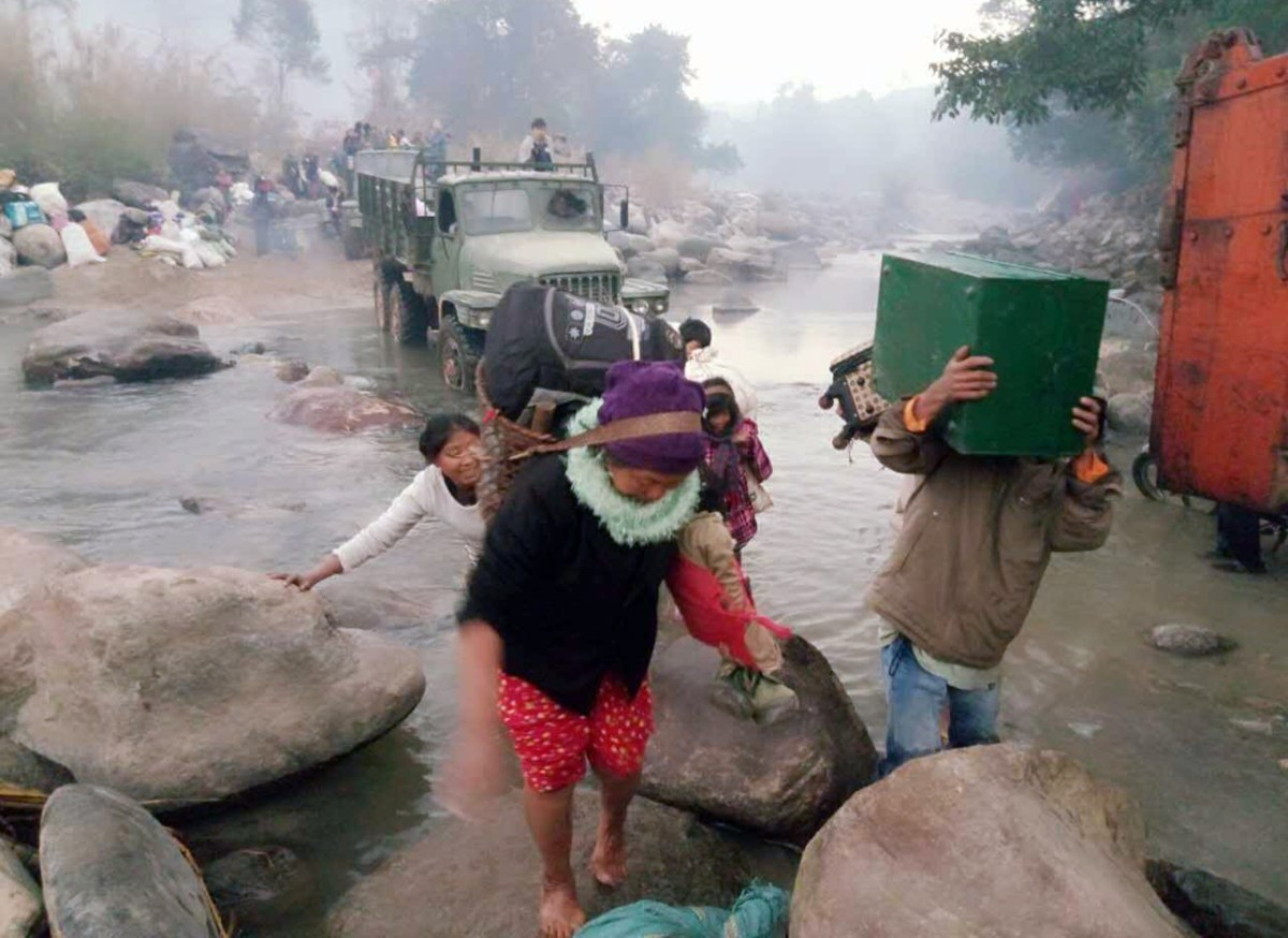 Myanmar residents displaced from fighting between ethnic rebel groups and military troops arriving by foot and local trucks to cross the river boundary between Myanmar and China at the border village of Lung Byen near China's Yunnan province. Photo: AFP/Joint Strategy Team/handout