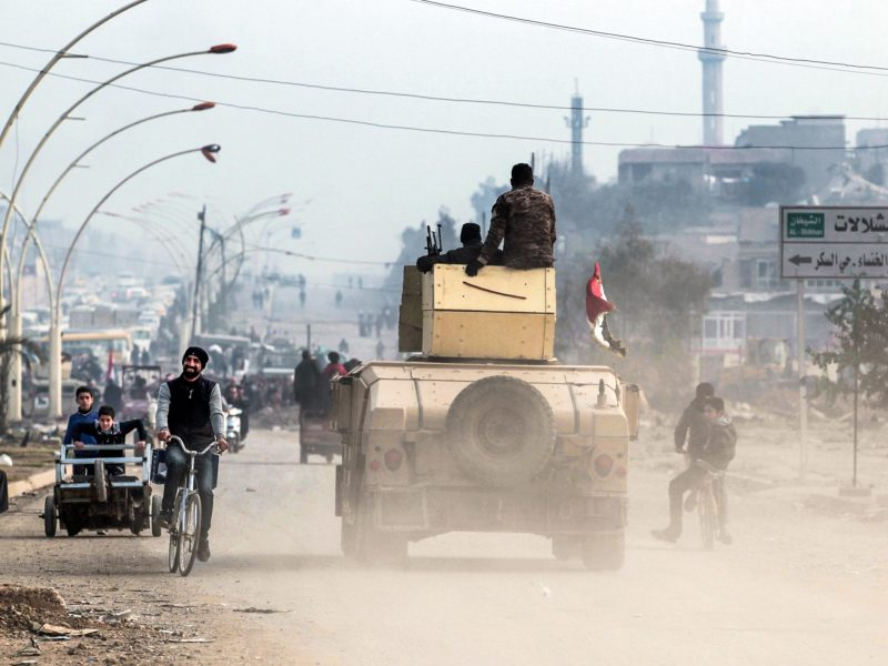 An man cycles past an Iraqi forces humvee driving on a street near the University of Mosul after its liberation from the Islamic state group (ISIS) control, during the ongoing military operation against the jihadists, on January 21, 2017. Photo: AFP/Ahmad al-Rubaye