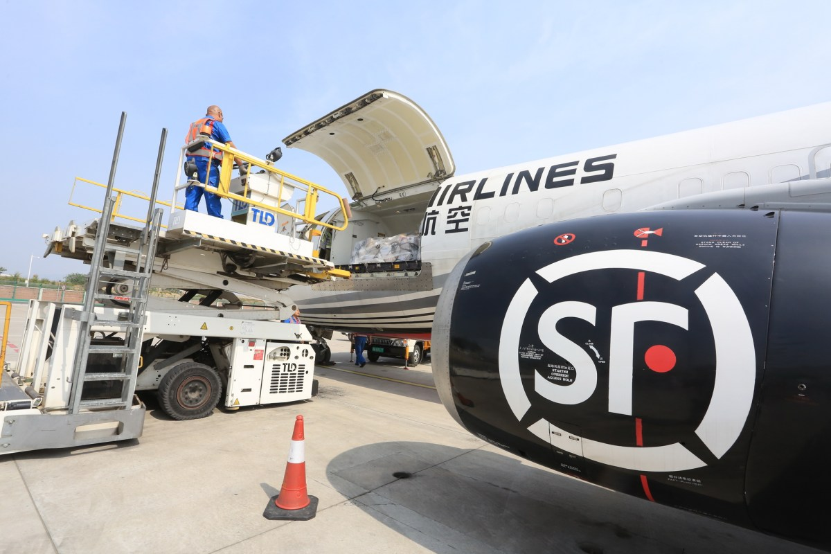 A Chinese worker loads parcels onto a cargo plane of SF Airlines at the Dalian Zhoushuizi International Airport in Dalian city, northeast China's Liaoning province, 8 June 2016. Photo: AFP/Zhang Chunlei