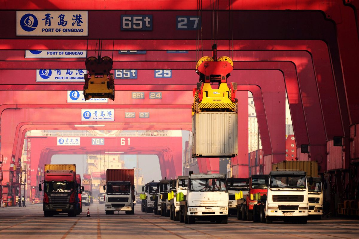 Crane vehicles lift containers to be shipped abroad from trucks on a quay at the Port of Qingdao in Qingdao city, Shandong province.Photo: AFP