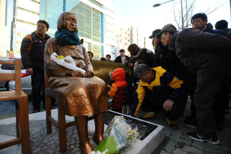 Flowers are laid on a statue of a girl that represents the wartime sexual victims by the Japanese military, during a rally in front of Japanese Consulate in Busan, South Korea, on December 30, 2016. Photo: Reuters