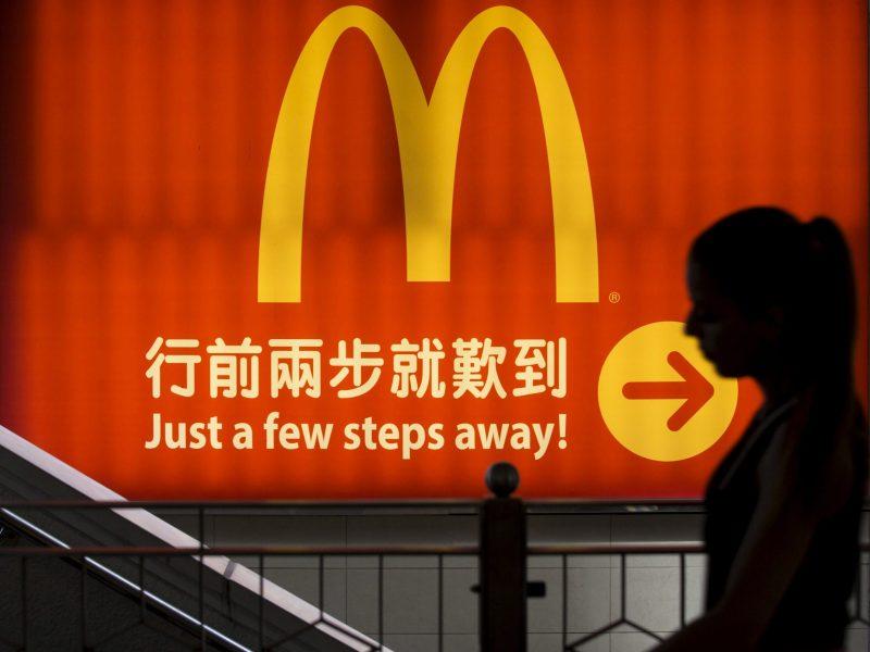 FILE PHOTO: A woman walks past a McDonald's outlet in Hong Kong, China July 25, 2014. REUTERS/Tyrone Siu/File Photo