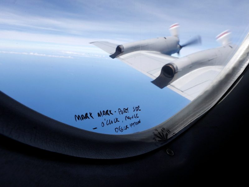 Handwritten notes on how a crew member should report the sighting of debris in the southern Indian Ocean is pictured on a window aboard a Royal New Zealand Air Force P-3K2 Orion aircraft searching for missing Malaysian Airlines flight MH370. Photo: Reuters/Jason Reed