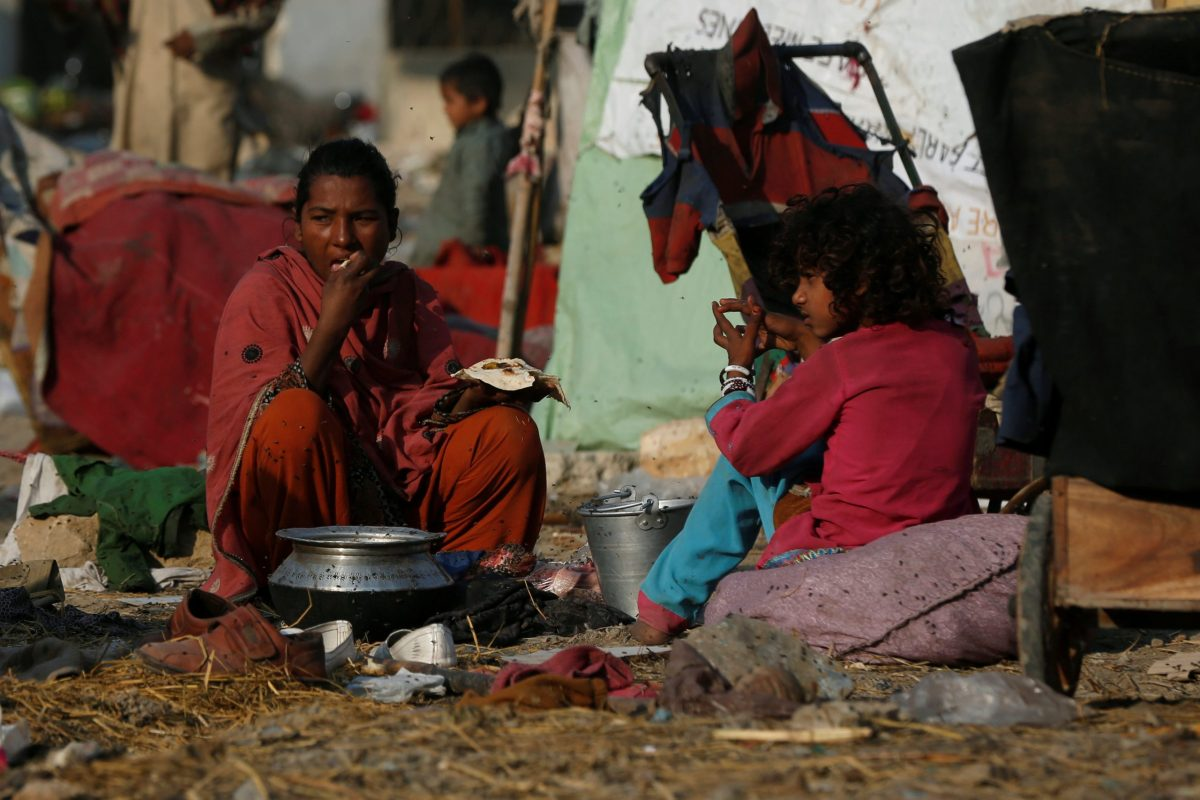 A woman eats her lunch of bread and curry outside her makeshift tent near a fruit market in Karachi, Pakistan January 18, 2017. REUTERS/Akhtar Soomro