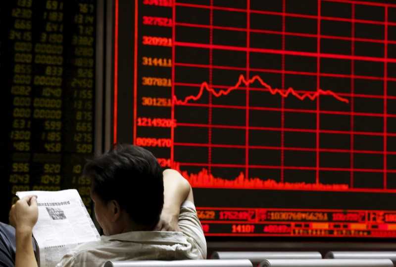 An investor sits by the board at a brokerage house in Beijing. Photo: Reuters / Kim Kyung-Hoon