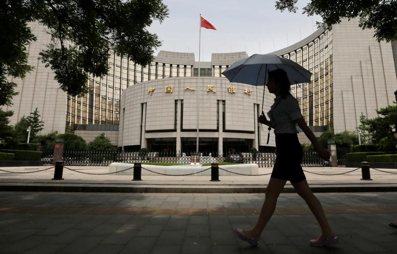 China is a bank-led economy, so it's debt profile differs from the US. Woman walks past the headquarters of the PBOC in Beijing. Photo: Reuters