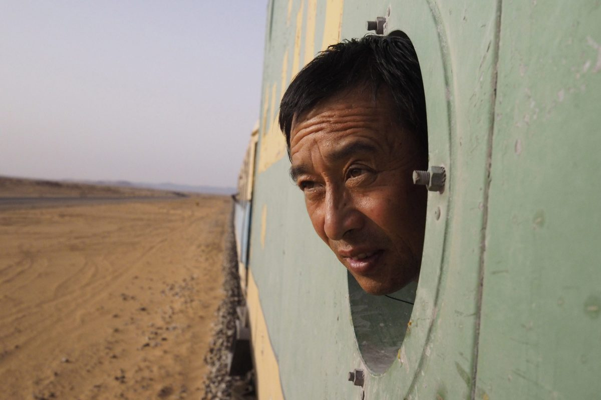 A Chinese businessman looks out the window on board an SNIM train carrying iron ore and mine workers across the desert outside Zouerate in Mauritania. Photo: REUTERS / Joe Penney