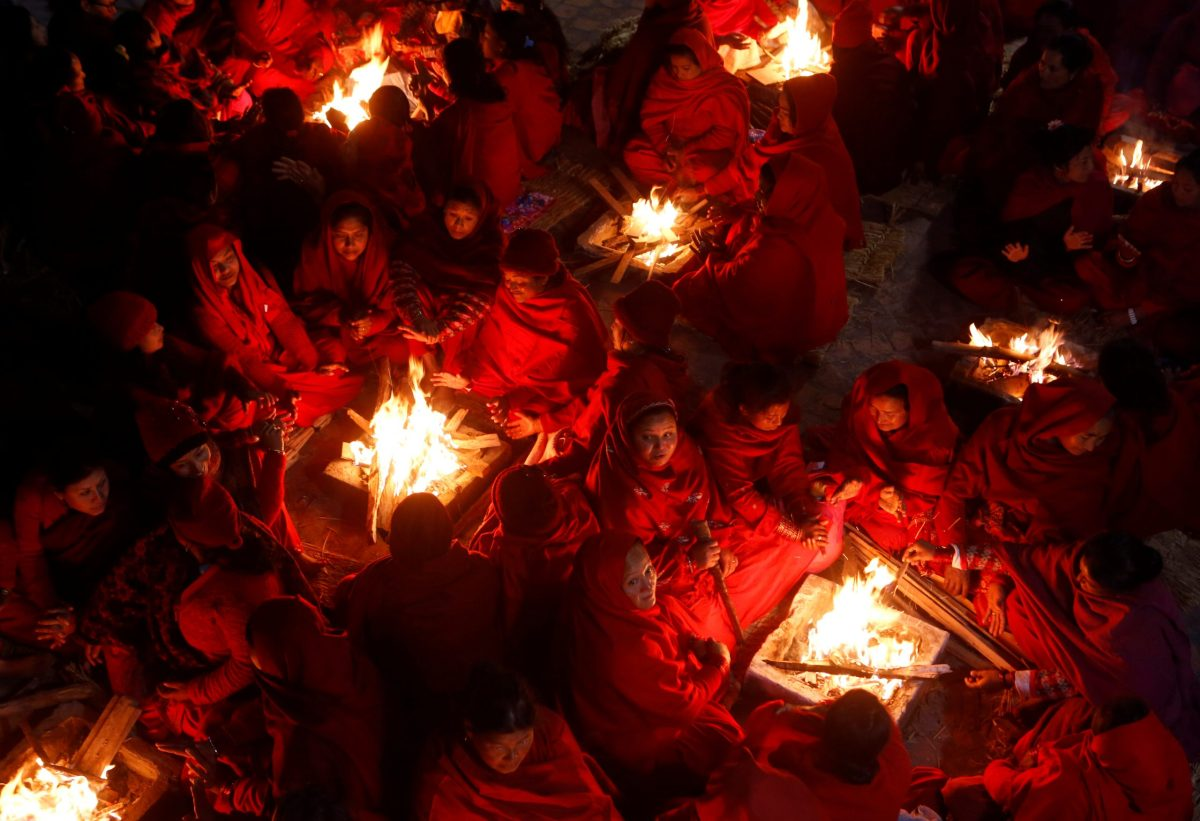Hindu women sit around fires to keep warm before taking holy baths at Saali River during the Swasthani Brata Katha festival at Sankhu in Kathmandu, Nepal, January 12, 2017.  REUTERS/Navesh Chitrakar     TPX IMAGES OF THE DAY - RTX2YKYD