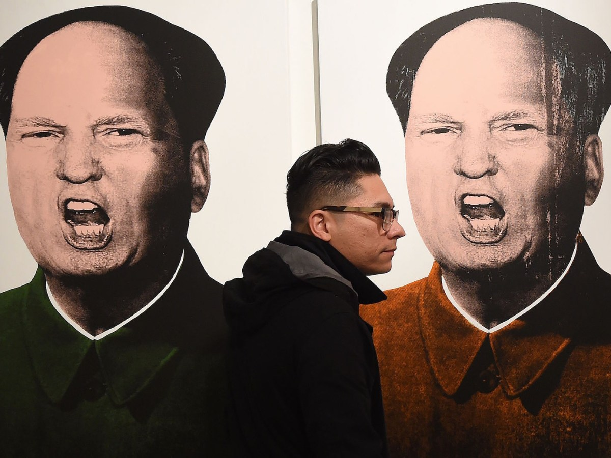 An art lover walks past a series of images titled 'Mao Trump' by contemporary pop artist Knowledge Bennett at the Ren Gallery display during the LA Art Show in Los Angeles, California on January 31, 2016.  Mark Ralston/AFP/Getty    Images