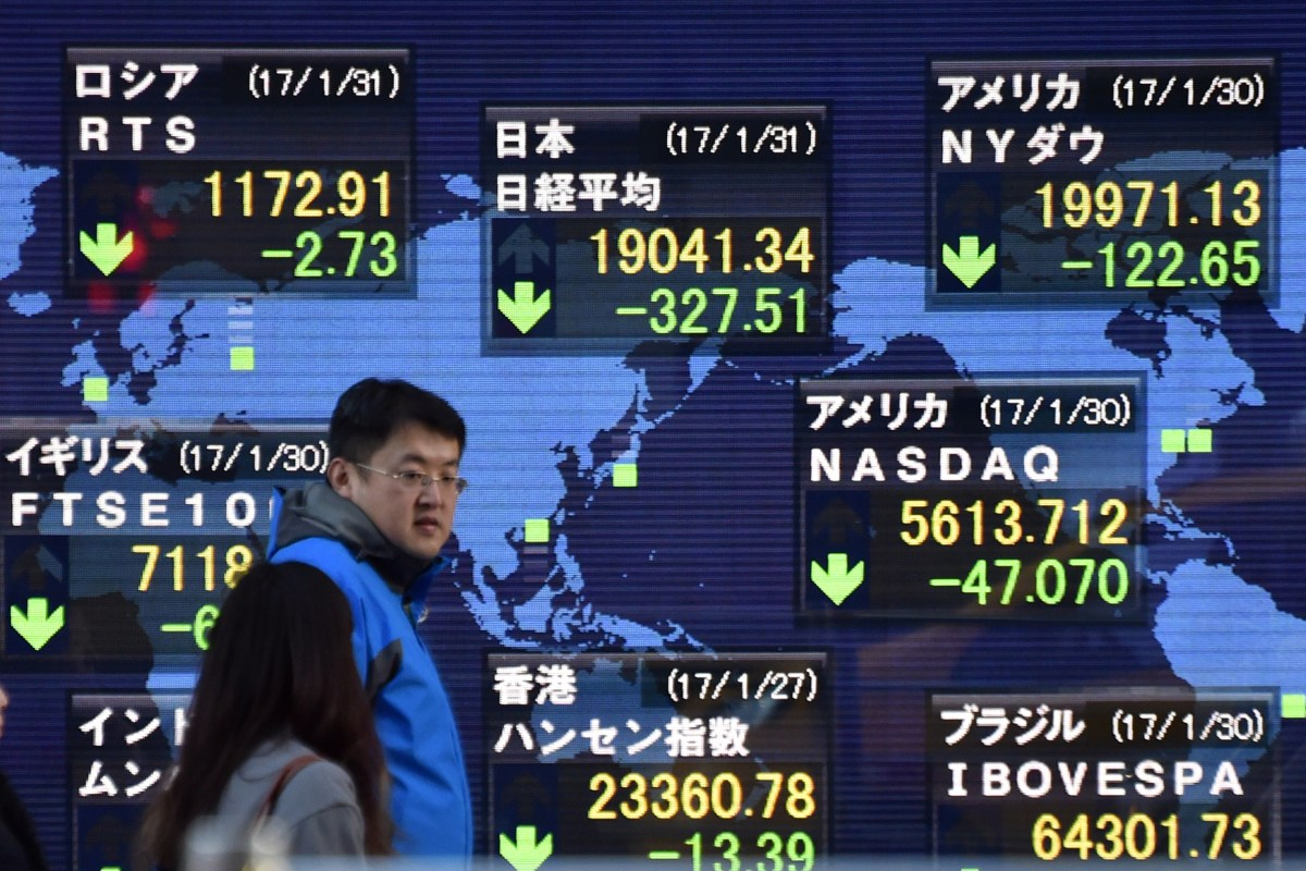 A man walks past a display of global stock indices (green for losses) in Tokyo. Photo: Kazuhiro Nogi/ AFP