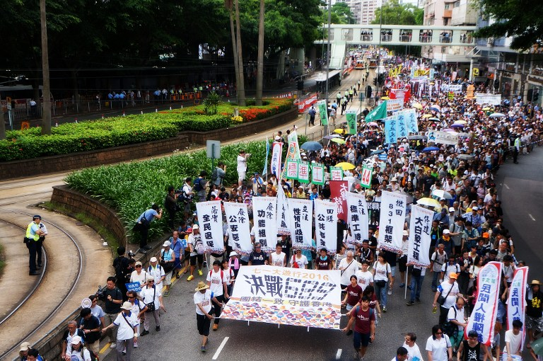 Tens of thousands of protesters attend an annual pro-democracy march in Hong Kongamid bookseller's safety fears on July 1, 2016.Protesters hold photos of Lam Wing Kee, one of five booksellers who went missing last year after publishing books critical of China's leaders. The case of the booksellershaveraised international concerns that Hong Kong's judicial independence and freedom of speech were being eroded.  Photo: P.H. Yang