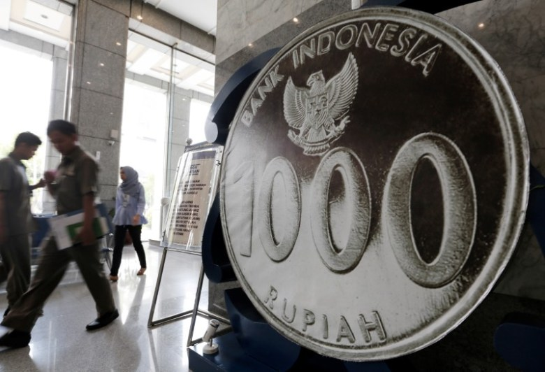 People walk past a mock one thousand Rupiah coin on display at Bank Indonesia's headquarters in Jakarta, Indonesia, November 17, 2016. Photo: Reuters / Beawiharta