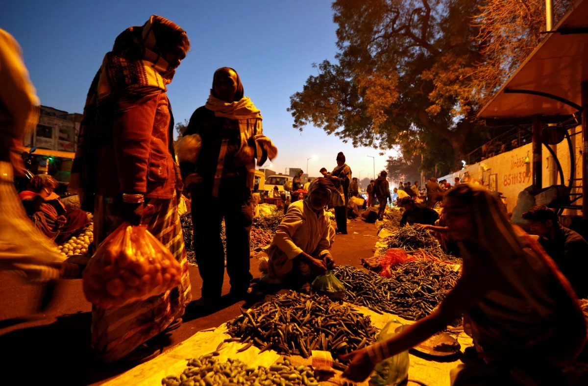 People buy vegetables from a roadside market in the early morning in Ahmedabad February 1, 2017. REUTERS/Amit Dave
