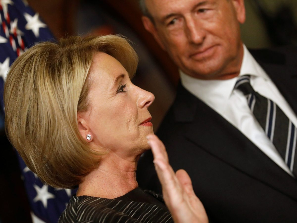 Betsy DeVos, joined by her husband Dick DeVos, is sworn in to be U.S. Education Secretary at the Eisenhower Executive Office Building at the White House in Washington, U.S. February 7, 2017. REUTERS/Jonathan Ernst