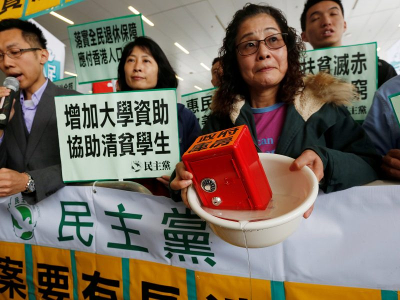A protester carries a safe in water to mock the government's fiscal policy before the release of the annual budget report in Hong Kong, China February 22, 2017.      Photo: Reuters/Bobby Yip