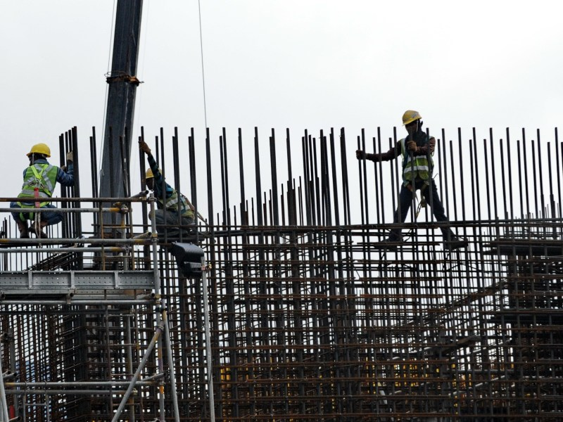 Laborers work at a construction site for an office building in Singapore. Photo: AFP / Roslan Rahman