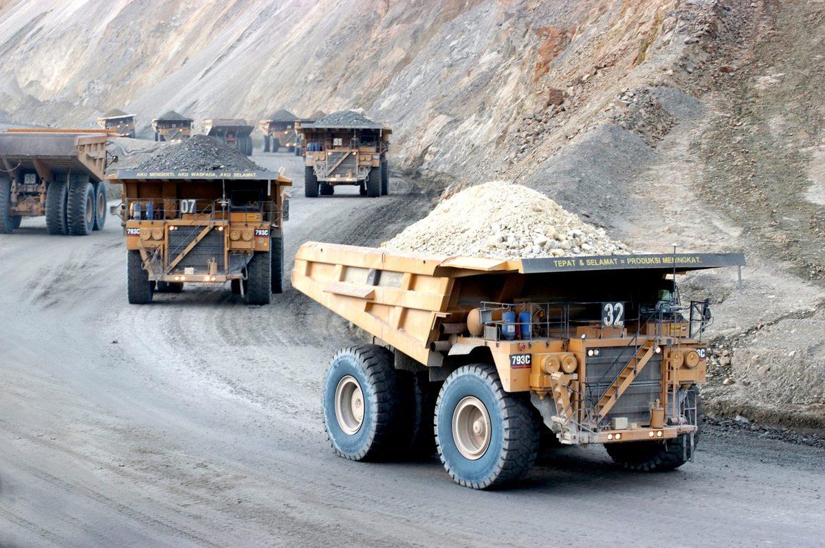 Trucks haul raw earth materials from copper mine site. Photo: AFP, PT Newmont Nusa Tenggara