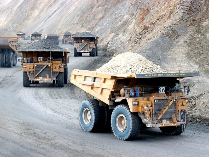 Trucks haul raw earth materials from copper mine site. Photo: AFP, PT Newmont Nusa Tenggara