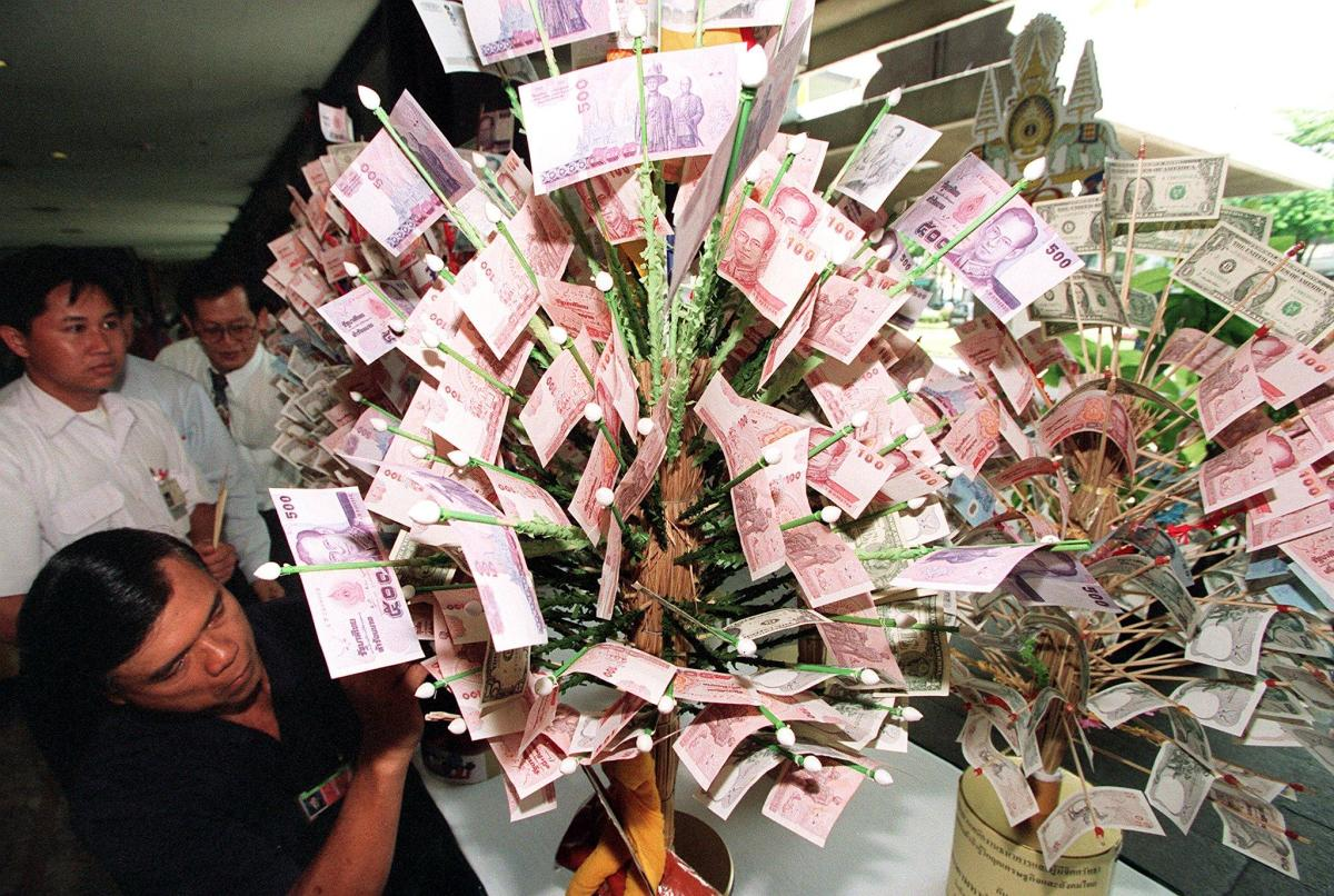 Bank of Thailand (BoT) officials arrange Thai baht bills onto ceremonious money trees. Thai companies and individuals are increasingly sending their capital overseas despite government measures to attract more private investment. Photo: AFP/ Pornchai Wittikongsakul