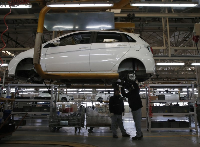Employees work on an assembly line producing electric cars at a factory in Beijing. Photo: Reuters/Kim Kyung-hoon
