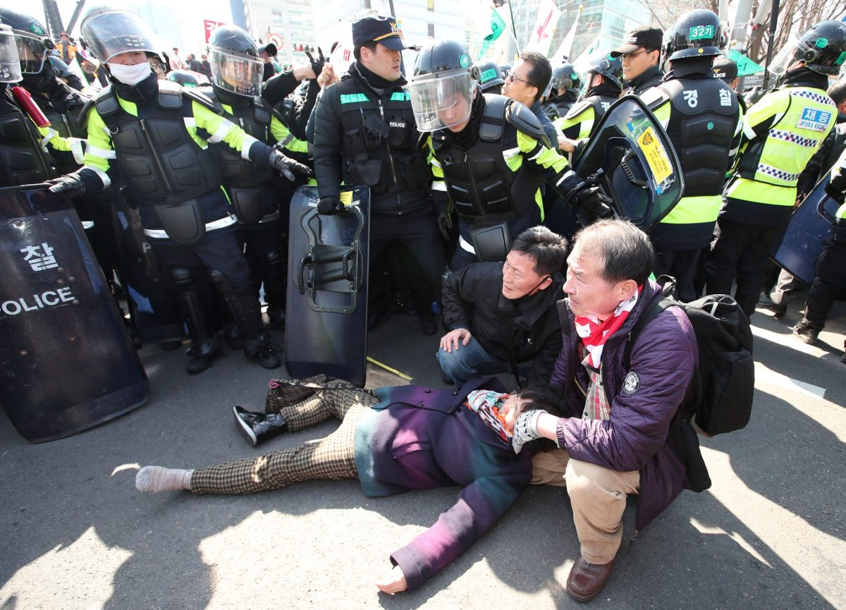 People take care of a protester who fainted during a march supporting South Korean President Park Geun-hye near the Constitutional Court in Seoul. Photo: Yonhap via Reuters