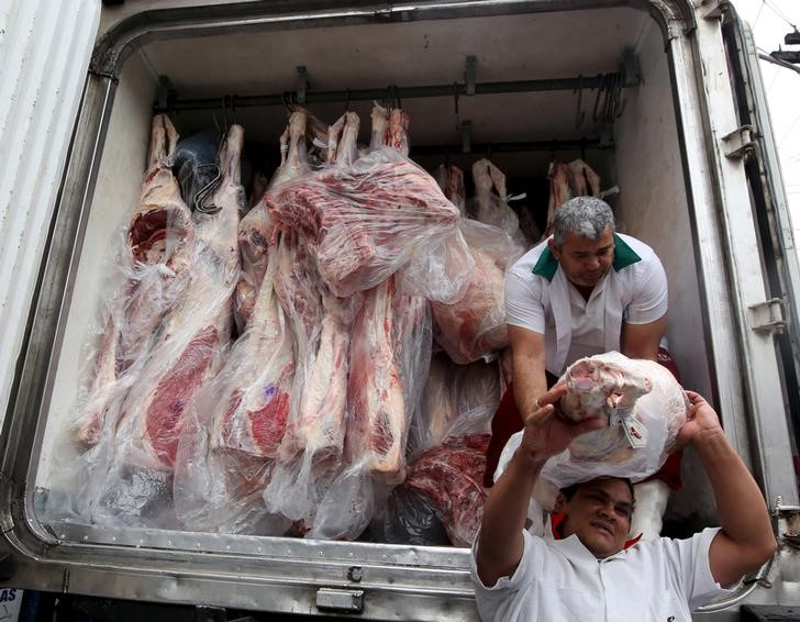 Workers unload packed meat from a truck in Sao Paulo, June 3, 2015. REUTERS/Paulo Whitaker