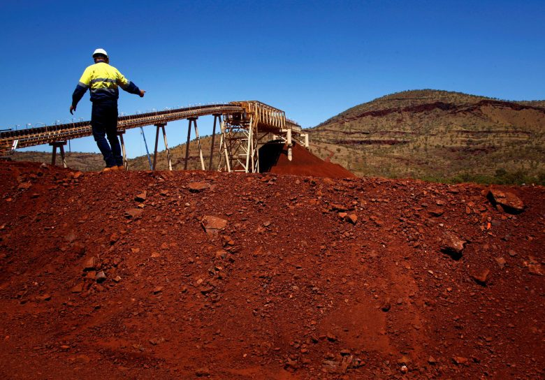 FILE PHOTO - Fortescue Chief Executive Officer (CEO) Nev Power climbs a pile of iron ore at the Fortescue Solomon iron ore mine located in the Valley of the Kings, around 400 km (248 miles) south of Port Hedland in the Pilbara region of Western Australia, December 2, 2013.  REUTERS/David Gray/File photo - RTX2YWV1