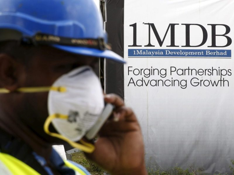 A construction worker talks on the phone in front of a 1Malaysia Development Berhad (1MDB) billboard at the Tun Razak Exchange development in Kuala Lumpur, Malaysia, February 3, 2016. Photo: Reuters/Olivia Harris