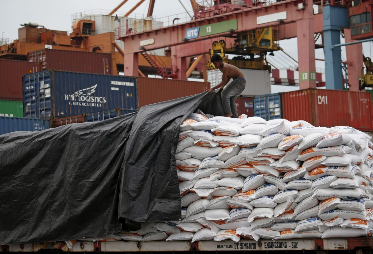 A worker covers sacks of rice imported from Vietnam. Photo: Reuters, Darren Whiteside