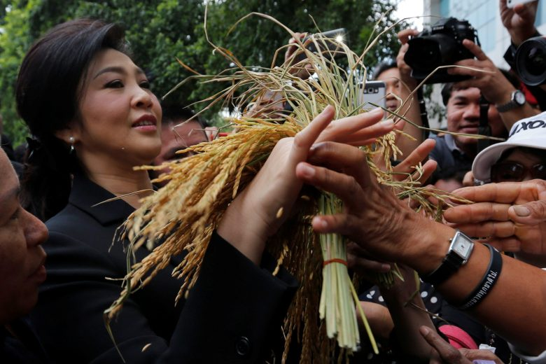 Ousted former Thai Prime Minister Yingluck Shinawatra receives ears of rice from her supporters as she arrives at the Supreme Court for a trial on criminal negligence looking into her role in a debt-ridden rice subsidy scheme during her administration, in Bangkok, Thailand November 4, 2016. REUTERS/Chaiwat Subprasom - RTX2RU77