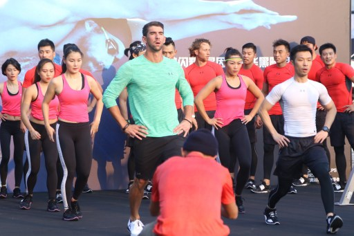 American swimming star Michael Phelps, center, practises during a promotional event for sportswear brand Under Armour in Shanghai, China, 7 November 2016.
