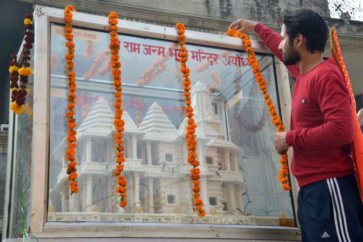 A member of an extremist Hindu organization garlands a model of a Ram temple on the 24th anniversary of the destruction of the Babri Masjid mosque in Ayodhya. India's Supreme Court has ordered resumption of a long-delayed conspiracy trial of Hindu hardliners in the mosque's 1992 demolition. Photo: AFP/ Narinder Nanu