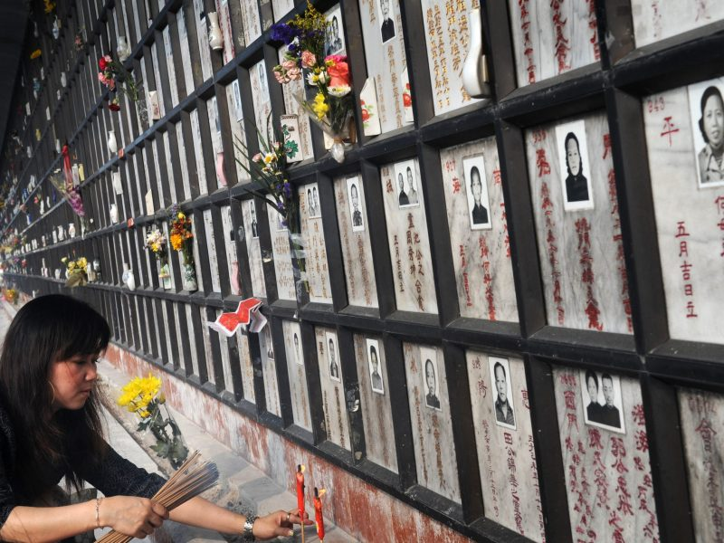 A woman lights candles and incense at the memorial niche of a relative at a cemetery in Hong Kong. Photo: AFP