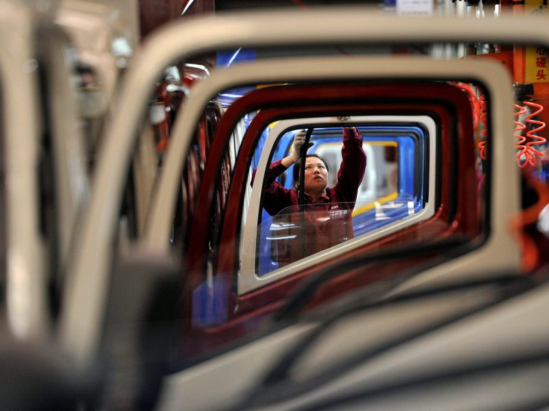 A worker installs rubber onto the windows of the doors along a production line at a truck factory of Anhui Jianghuai Automobile Co. Ltd (JAC Motors) in Hefei, Anhui province May 5, 2014.   Photo: Reuters/Stringer